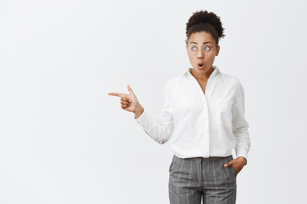 Impressed and surprised attractive dark-skinned female with curly hair in glasses and white collar shirt, holding hand in pocket, folding lips from curiosity, looking and pointing left