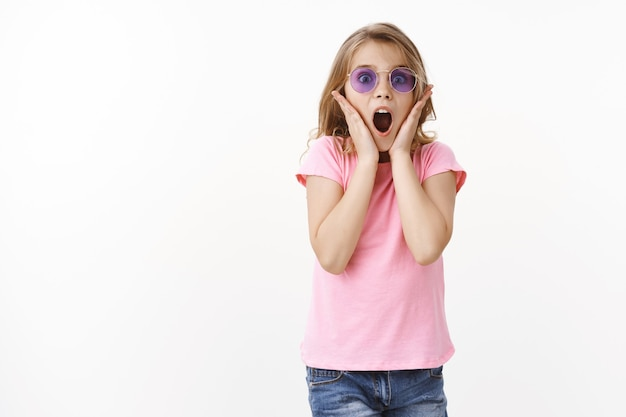 Impressed and surprised glamour young pretty kid, girl scream shocked and astonished, look camera admiration, amused awesome concert favorite children band, wear sunglasses hold hands on face