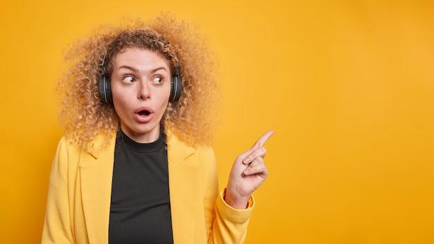 Впечатленная удивленная красивая женщина с густыми кудрявыми волосами показывает в верхнем правом углу, что она очень удивлена, демонстрирует удивительное предложение в официальной одежде, слушает музыку в наушниках.