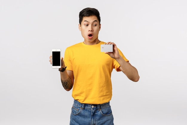 Impressed and surprised good-looking asian, chinese hipster guy in yellow t-shirt, holding phone and credit card, stare at banking card with wow face, gasping astonished, white wall