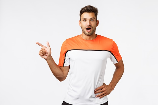 Impressed, surprised good-looking bearded man in sports t-shirt