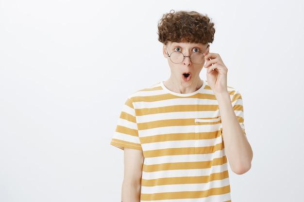 Ragazzo adolescente impressionato e sorpreso in posa contro il muro bianco
