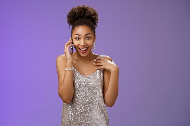 Впечатленная разговорчивая очаровательная афроамериканка в блестящем серебряном вечернем платье указывая на себя удивленно удивленно улыбаясь говорящий смартфон широко раскрывает глаза изумленно, стоя на синем фоне.