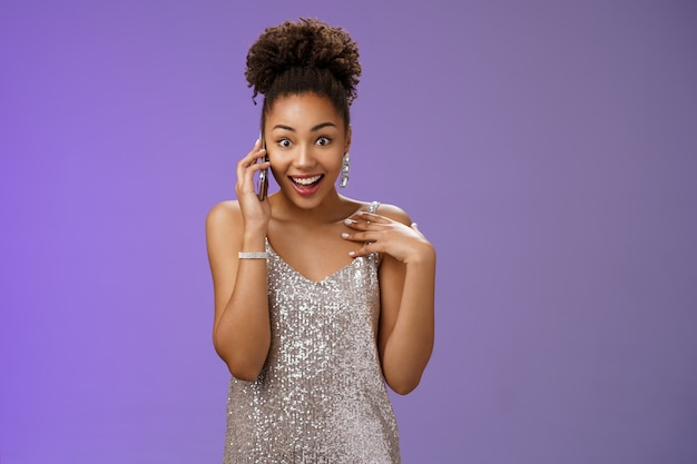 Impressionato loquace affascinante donna afro-americana in abito da sera argento lucido che indica se stessa divertito sorpreso sorridente parlando smartphone allargare gli occhi stupiti, in piedi sfondo blu.