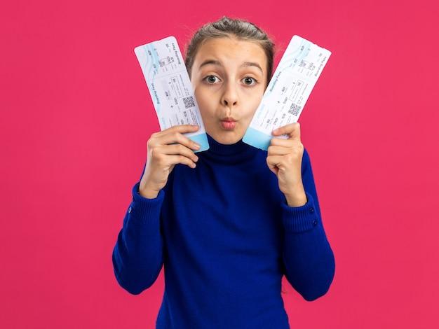 ピンクの壁に分離された口すぼめ呼吸で彼らと顔に触れる飛行機のチケットを保持している感動の10代の少女