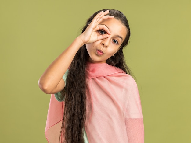 올리브 녹색 벽에 고립 된 표정 제스처를 하 고 목도리를 입고 감동 10 대 소녀