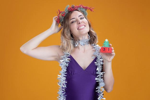 茶色の背景で隔離の頭に手を置くクリスマスのおもちゃを保持している首に花輪と紫色のドレスと花輪を身に着けている印象的な傾斜頭の若い美しい少女