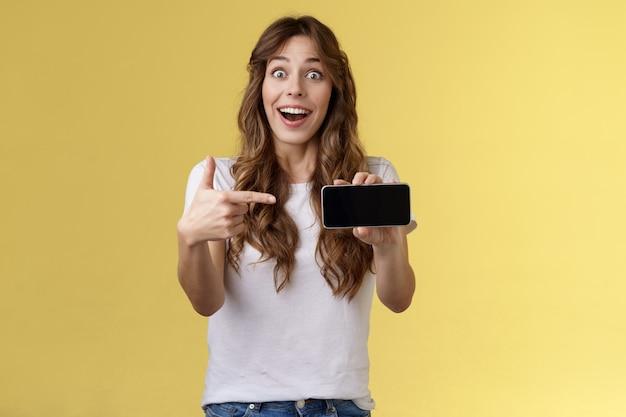 Impressionato ottimista felice fortunata ragazza riccia acconciatura lunga bocca aperta ammirazione gioia come fantastica nuova app mostra smartphone schermo orizzontale telefono espositore sfondo giallo stupito