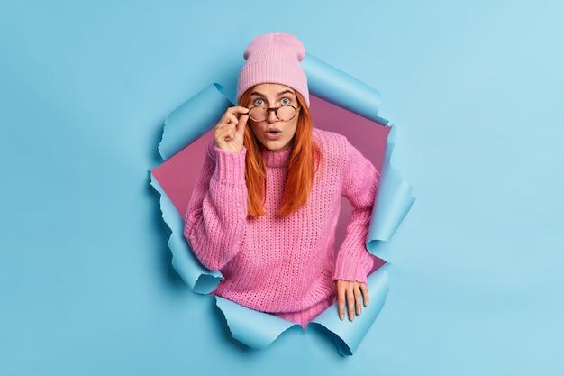 인상적인 여성은 놀랍게 보이고 놀란 느낌, 분홍색 모자 니트 스웨터를 입고 종이를 뚫습니다.