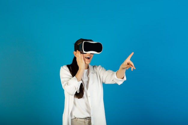 Impressed woman in virtual reality glasses plays a video game and points with her index finger