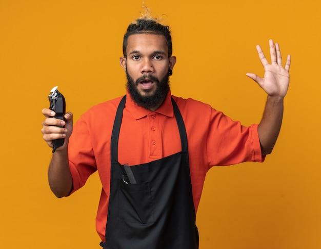 手で5つを示すバリカンを保持している制服を着ている感銘を受けた若いアフリカ系アメリカ人の床屋