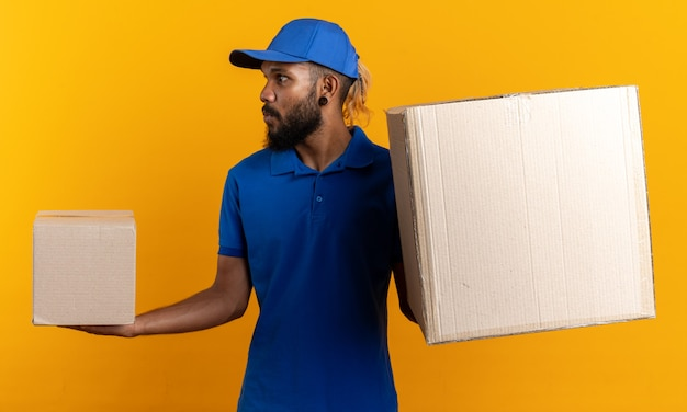 Impressed young afro-american delivery man holding cardboard boxes looking at side isolated on orange wall with copy space