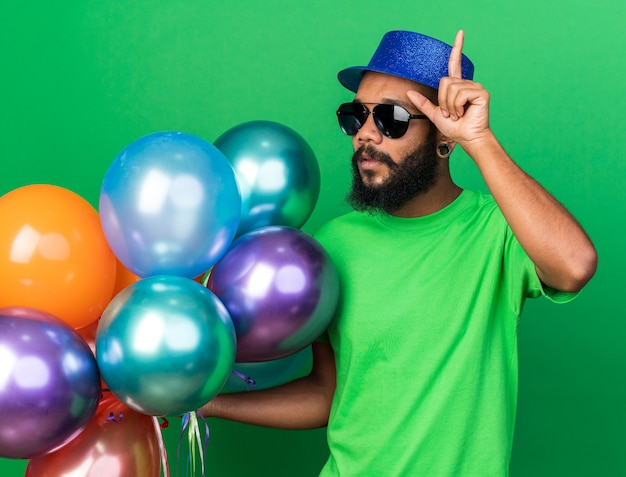Impressed young afro-american guy wearing party hat and glasses holding balloons points up
