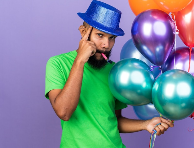 Impressed young afro-american guy wearing party hat holding balloons blowing party whistle putting finger on temple isolated on blue wall