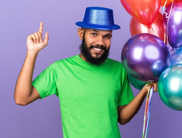 Impressed young afro-american guy wearing party hat holding balloons points at up