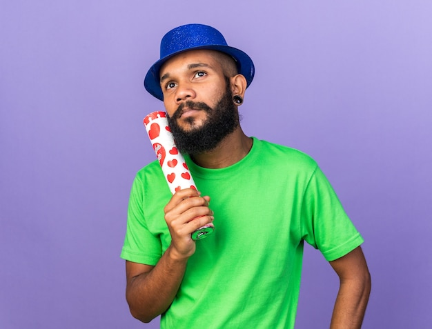 Impressed young afro-american guy wearing party hat holding confetti cannon isolated on blue wall