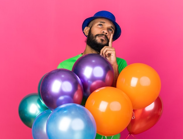 Impressed young afro-american guy wearing party hat standing behind balloons isolated on pink wall