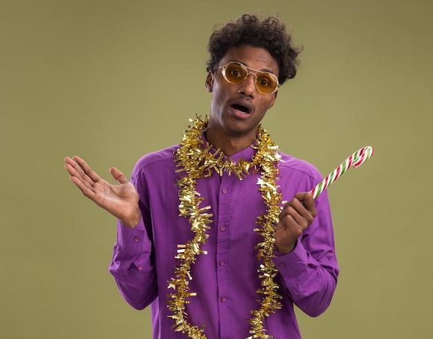 オリーブグリーンの背景に分離された空の手を示すカメラを見てクリスマスキャンディケインを保持している首の周りに見掛け倒しの花輪と眼鏡をかけている印象的な若いアフリカ系アメリカ人の男