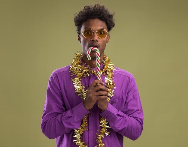 オリーブグリーンの背景に分離されたカメラを見て口の近くにクリスマスキャンディケインを保持している首の周りに見掛け倒しの花輪と眼鏡をかけている印象的な若いアフリカ系アメリカ人