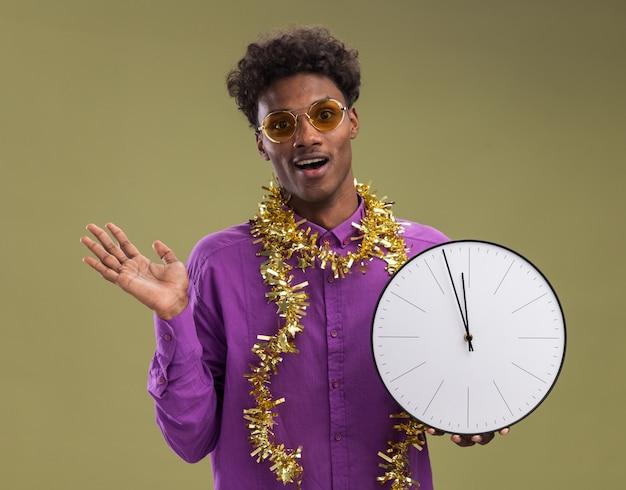 Впечатленный молодой афро-американский мужчина в очках с гирляндой из мишуры на шее держит часы, глядя в камеру, показывая пустую руку, изолированную на оливково-зеленом фоне