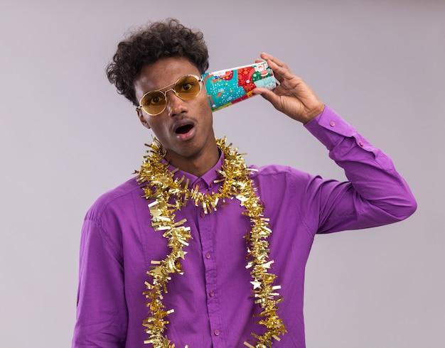 흰색 배경에 고립 된 카메라를보고 대화를 듣고 귀 옆에 플라스틱 크리스마스 컵을 들고 목 주위에 반짝이 갈 랜드와 안경을 쓰고 감동 젊은 아프리카 계 미국인 남자
