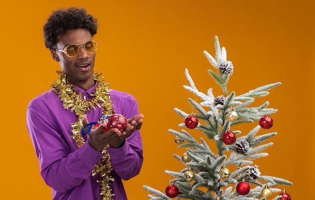 Впечатленный молодой афро-американский мужчина в очках с гирляндой из мишуры на шее, стоящий возле украшенной рождественской елки, держа и глядя на рождественские безделушки, изолированные на оранжевом фоне