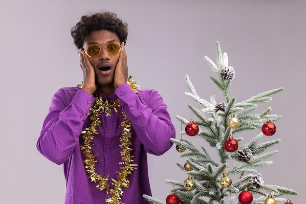 Impressionato giovane afro-americano con gli occhiali con la ghirlanda di orpelli intorno al collo in piedi vicino all'albero di natale decorato tenendo le mani sul viso isolato sul muro bianco