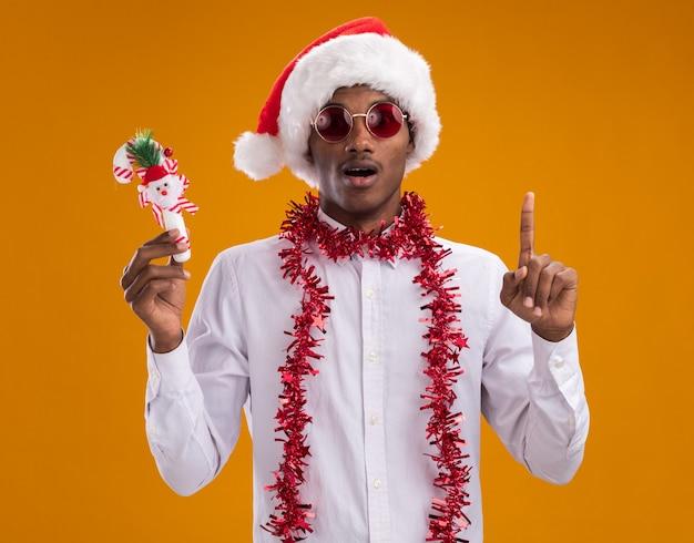 オレンジ色の背景に分離されたカメラを上向きに見ているキャンディケインの飾りを保持している首の周りに見掛け倒しの花輪とサンタの帽子と眼鏡を身に着けている印象的な若いアフリカ系アメリカ人の男