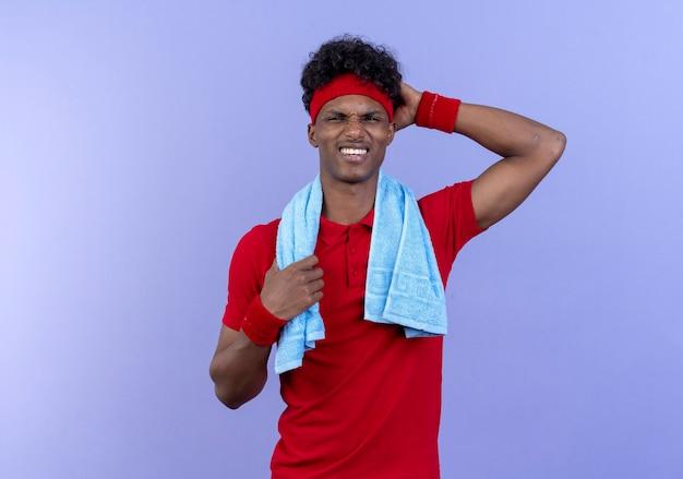 Ha impressionato il giovane uomo sportivo afroamericano che indossa la fascia e il braccialetto mettendo la mano sulla testa con l'asciugamano sulla spalla isolata sulla parete blu