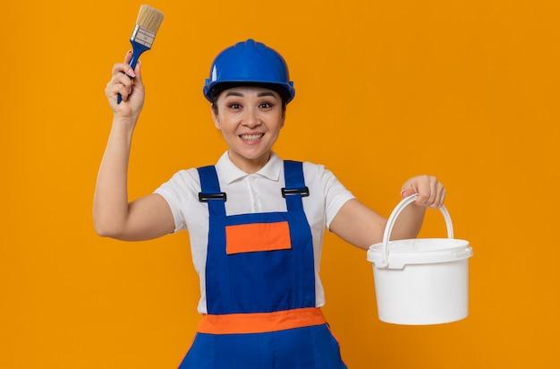 ペイントブラシと油絵の具を保持している青い安全ヘルメットを持つ感銘を受けた若いアジアのビルダーの女の子