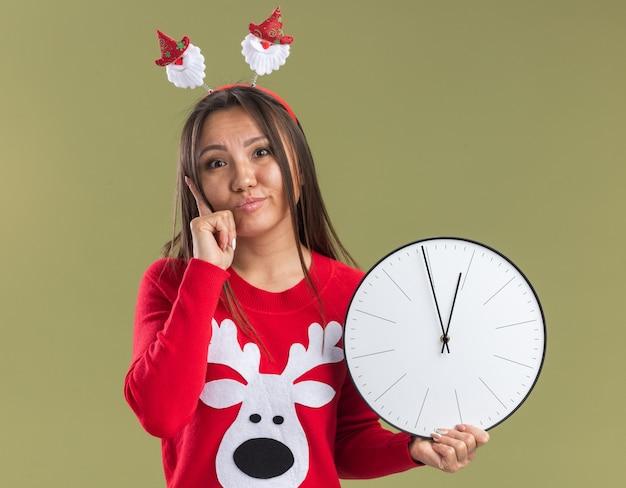 올리브 녹색 배경에 고립 뺨에 손가락을 넣어 벽 시계를 들고 크리스마스 머리 후프를 입고 감동 젊은 아시아 여자