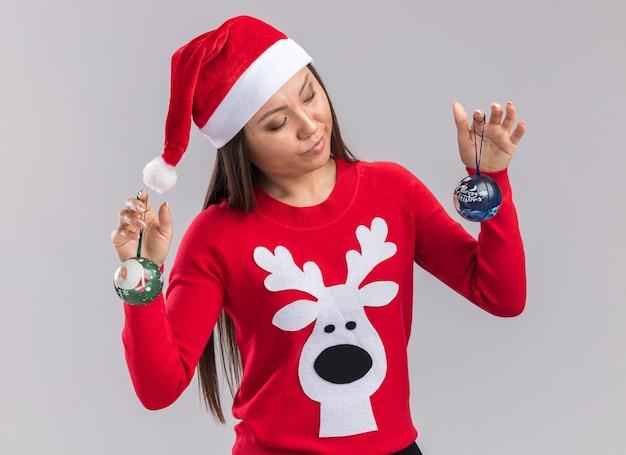 Впечатленная молодая азиатская девушка в новогодней шапке со свитером, держащая и смотрящую на елочные шары на белом фоне
