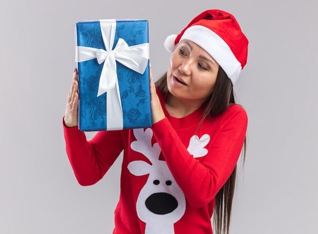 Впечатленная молодая азиатская девушка в рождественской шапке со свитером, держащей и смотрящей на подарочную коробку, изолированную на белом фоне