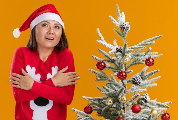 Впечатленная молодая азиатская девушка в новогодней шапке со свитером стоит рядом с елкой, скрещивая руки на оранжевом фоне