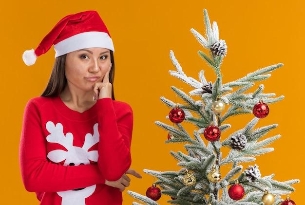 Impressionato giovane ragazza asiatica che indossa il cappello di natale con maglione in piedi vicino albero di natale mettendo il dito sulla guancia isolato su sfondo arancione
