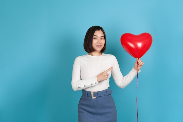 Impressed young asian woman holds a heart-shaped flying balloon and points at it with her index finger