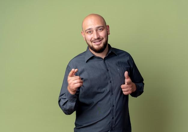 Impressionato giovane uomo calvo della call center che ti fa gesto isolato su verde oliva con lo spazio della copia