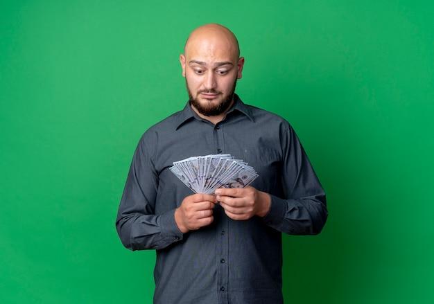 인상적인 젊은 대머리 콜 센터 남자 잡고 복사 공간이 녹색에 고립 된 돈을보고