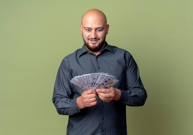 인상적인 젊은 대머리 콜 센터 남자 잡고 복사 공간이 올리브 그린에 고립 된 돈을보고