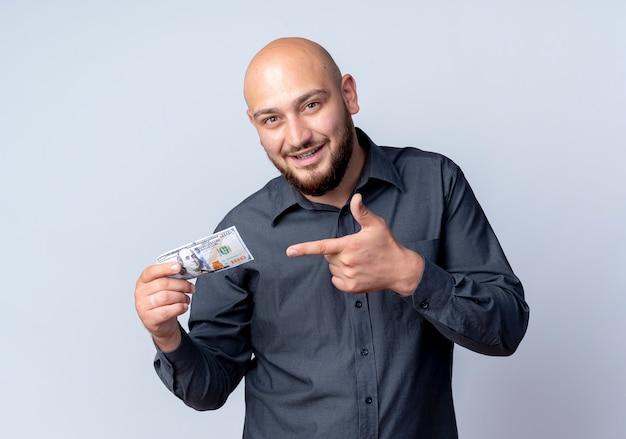 인상적인 젊은 대머리 콜센터 남자 잡고 돈을 흰색으로 격리 가리키는