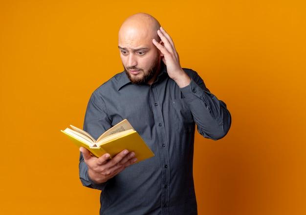 Impressionato giovane uomo calvo della call center che tiene e che esamina il libro con la mano sulla testa isolata sull'arancio con lo spazio della copia