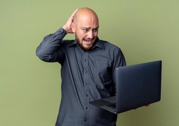 Impressionato giovane uomo calvo della call center che tiene e che esamina il computer portatile con la mano sulla testa isolata su verde oliva