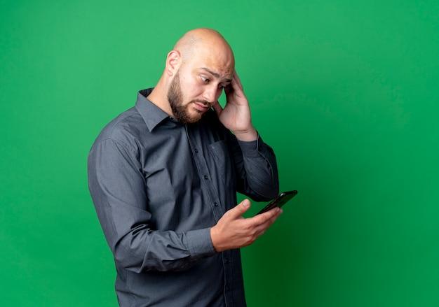 Impressionato giovane uomo calvo della call center che tiene e guardando il telefono cellulare e toccando la testa isolata sul verde con lo spazio della copia