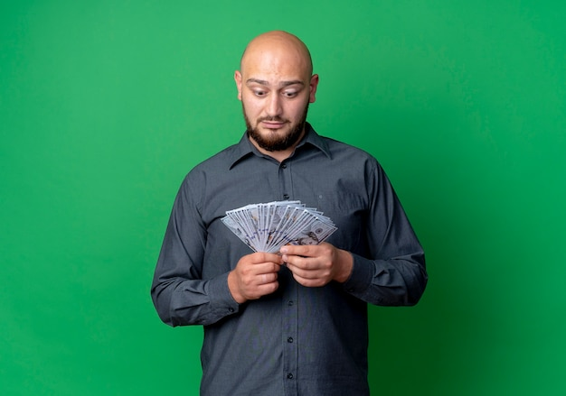 Impressed young bald call center man holding and looking at money isolated on green  with copy space