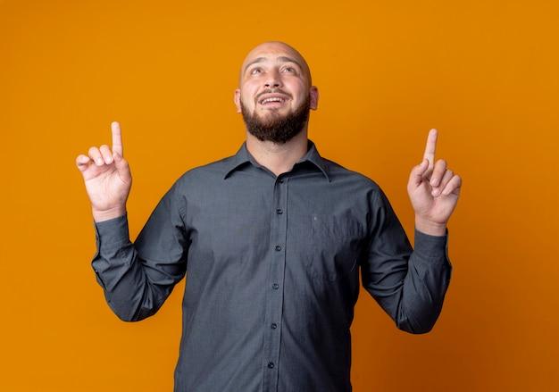 Impressionato giovane uomo calvo della call center che osserva e che indica in su isolato sull'arancio