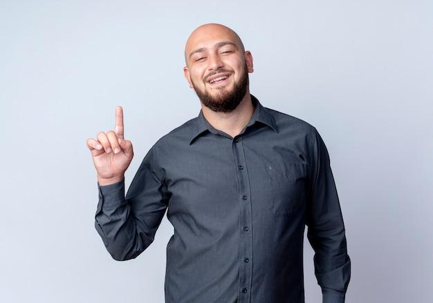Impressionato giovane uomo calvo call center rivolto verso l'alto isolato su bianco