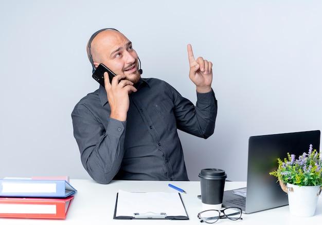 작업 도구와 책상에 앉아 헤드셋을 착용하고 감동 된 젊은 대머리 콜센터 남자는 전화를 들고 손가락으로 이야기하고 흰색에 고립 된 측면을보고