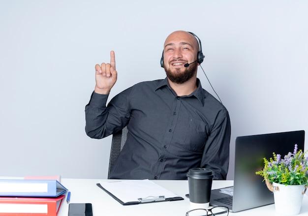 Impressionato giovane uomo calvo della call center che indossa la cuffia avricolare che si siede allo scrittorio con gli strumenti di lavoro che guardano e che indicano in su isolato su bianco
