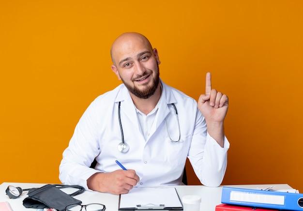 Impressionato giovane medico maschio calvo che indossa abito medico e stetoscopio seduto alla scrivania