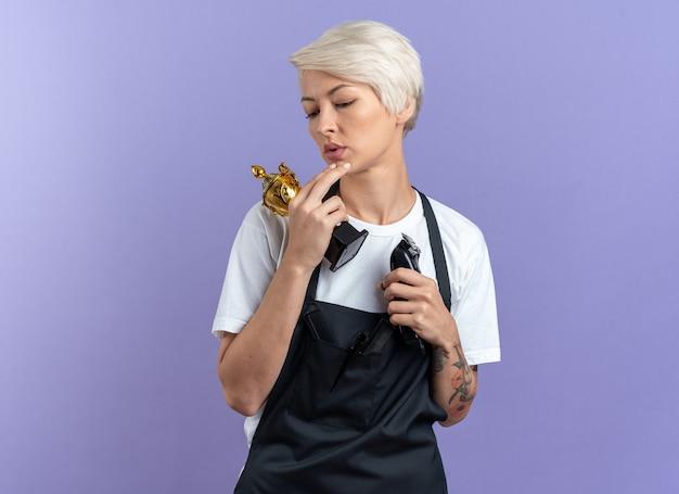 Впечатленная молодая красивая женщина-парикмахер в униформе, держащая кубок победителя с машинкой для стрижки волос, изолированной на синей стене